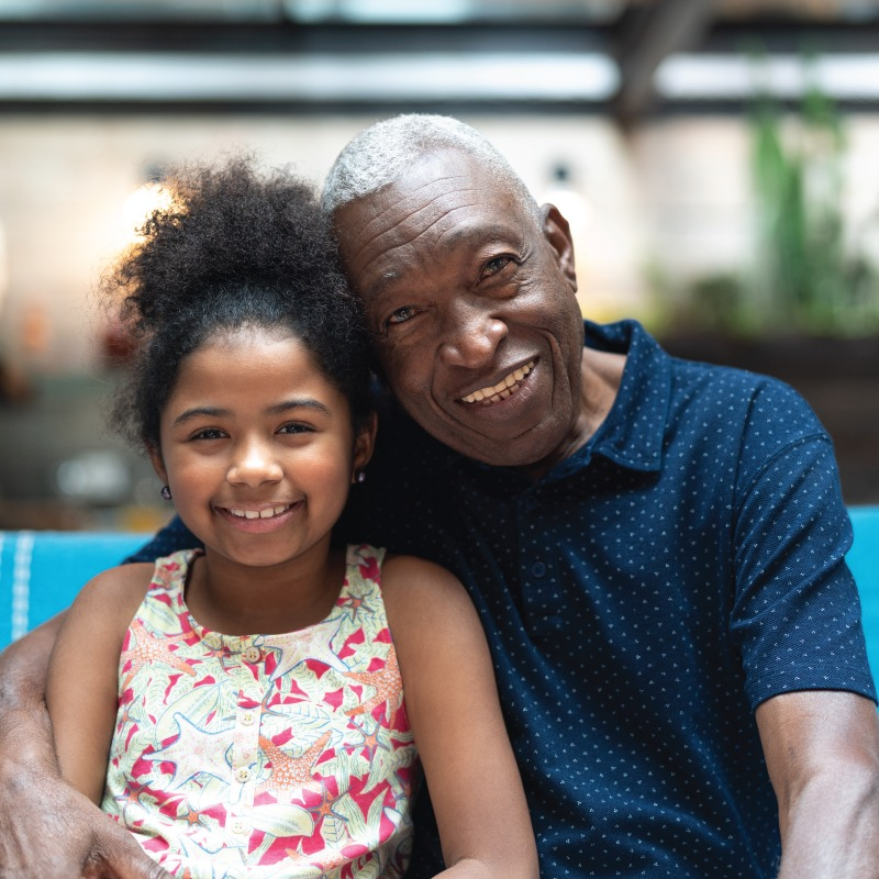 Elderly black man sitting next to his great granddaughter and smiling.
